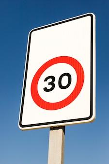 Close-up van nummer 30 verkeersbeperkteken tegen blauwe hemel