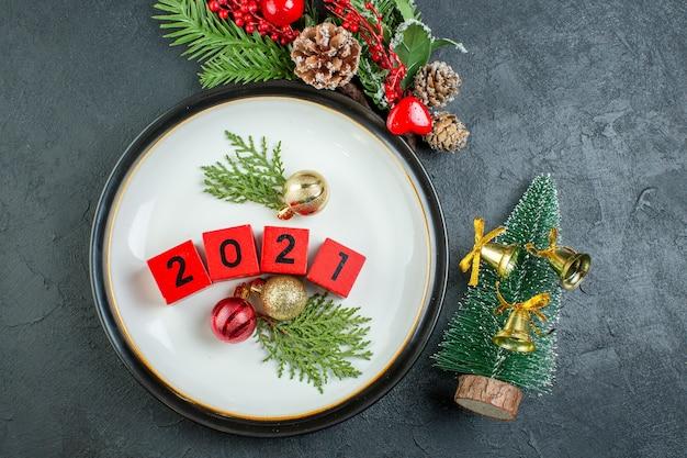 Close-up van nummers decoratie accessoires op een plaat fir takken conifeer kegel op donkere achtergrond