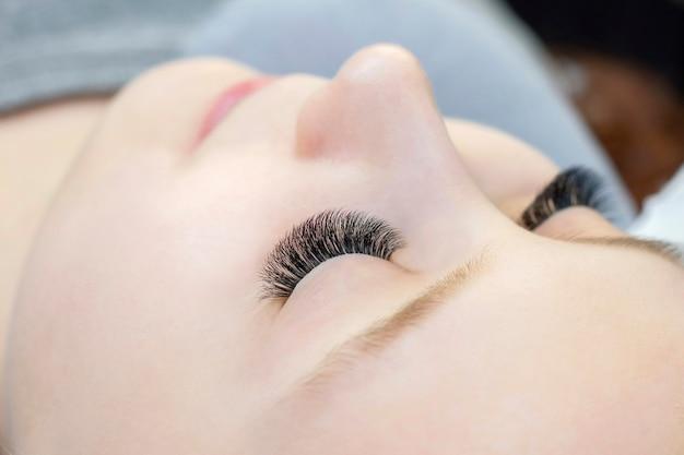 Close-up van ogen met uitgebreide wimpers en zonder uitgebreide wimpers, wit meisje. voor en na