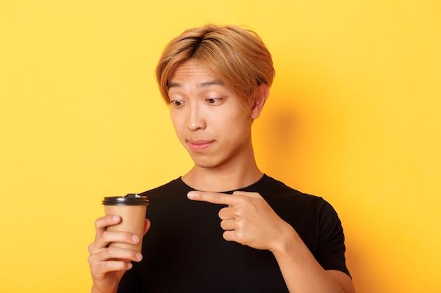 Close-up van onder de indruk knappe aziatische man wijzende vinger op heerlijke koffie