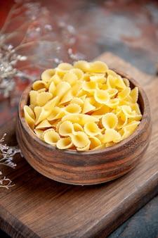 Close-up van ongekookte pasta's op houten snijplank op gemengde kleurentafel