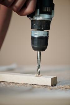Close-up van onherkenbaar meubelmaker boren houten plank in schrijnwerkerij workshop