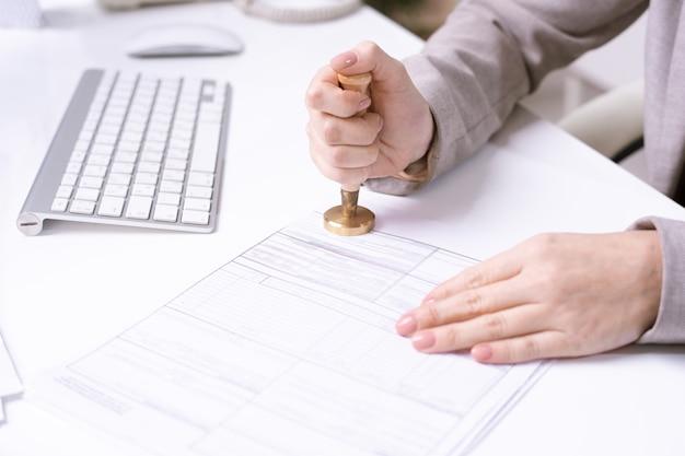 Close-up van onherkenbaar secretaresse zittend aan tafel met computertoetsenbord en stempelen aanvraagformulier