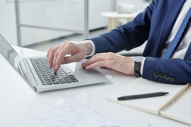 Close-up van onherkenbaar zakenman in jasje zit aan bureau met kladblok en typen op laptop in kantoor