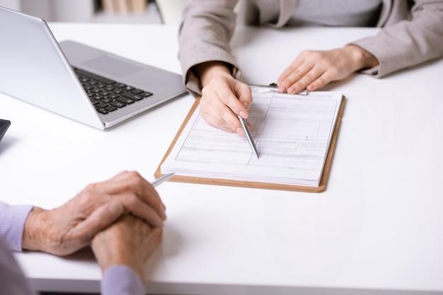 Close-up van onherkenbare adviseur die aan bureau met laptop zit en bejaarde cliënt bijstaat om document in te vullen Premium Foto