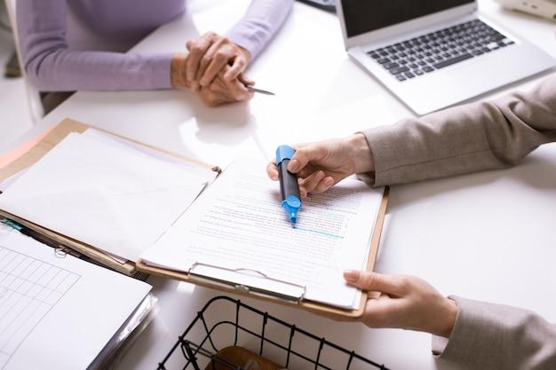 Close-up van onherkenbare adviseur die tekst in contract voor klant markeert terwijl hij het belangrijkste punt uitlegt