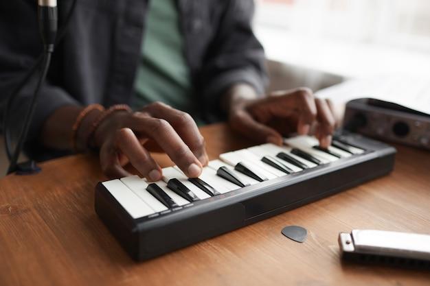 Close-up van onherkenbare afro-amerikaanse man muziek afspelen op toetsenbord tijdens het componeren thuis, kopieer ruimte
