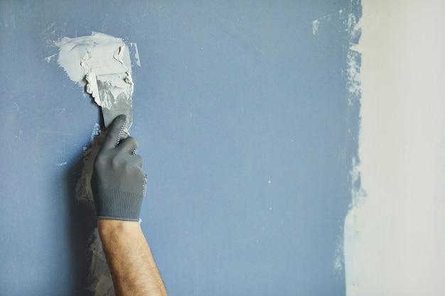Close-up van onherkenbare bouwvakker die droge muur gladstrijkt tijdens het renoveren van huis, kopie ruimte