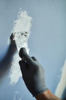 Close-up van onherkenbare bouwvakker droge muur bouwen tijdens het renoveren van huis, kopieer ruimte