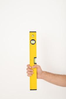 Close-up van onherkenbare hersteller die geel bouwniveau houdt tegen geïsoleerde achtergrond