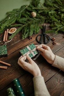 Close up van onherkenbare jonge vrouw die kerstcadeaus inpakt op rustieke houten tafel kopieerruimte