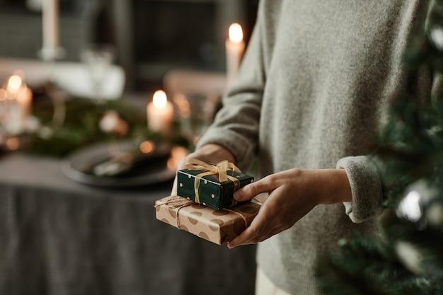 Close up van onherkenbare jonge vrouw met kleine kerstcadeautjes in kamer versierd met kaarsen...