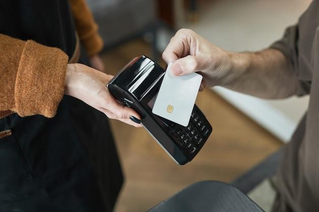 Close-up van onherkenbare klant die met contactloze kaart betaalt en deze op de terminal zet die wordt vastgehouden door serveerster in café