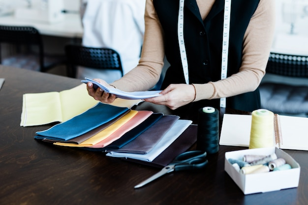 Close-up van onherkenbare kleermaker met meetlint rond hals die textiel voor kleding in studio kiest