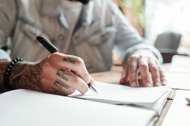 Close-up van onherkenbare man aan tafel zitten en plannen opschrijven in kladblok