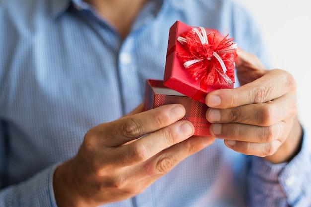 Close-up van onherkenbare man die kleine rode doos opent