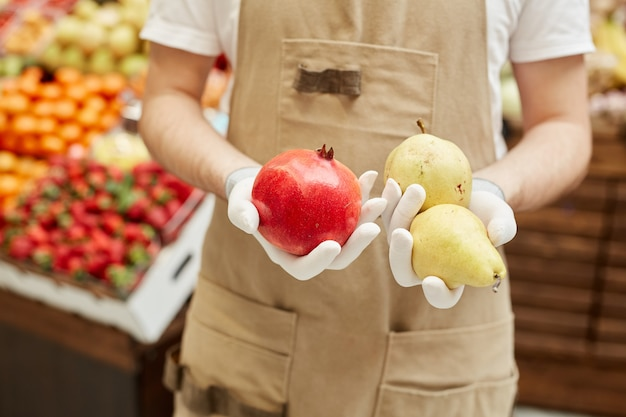 Close up van onherkenbare man die verse peren en granaatappel houdt terwijl hij groenten en fruit verkoopt op de boerenmarkt