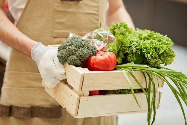 Close-up van onherkenbare man met doos met groenten tijdens de verkoop van verse producten op de boerenmarkt