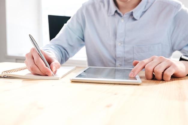 Close-up van onherkenbare marketeer die aan bureau zit en tablet gebruikt tijdens het werken met sociale media