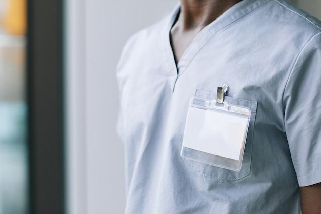 Close up van onherkenbare medische werker met een blanco id op uniform, kopieer ruimte