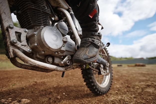 Close-up van onherkenbare motorrijder die voet op pedaal houdt tijdens het buiten lanceren van motor