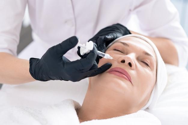 Close-up van onherkenbare schoonheidsspecialist die een spuit gebruikt tijdens het injecteren van vulmiddel in het gezicht van vrouwen om haar huid te verjongen