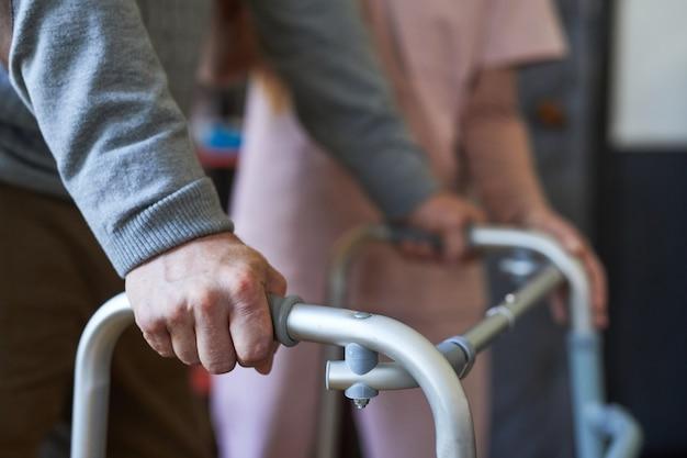 Close up van onherkenbare senior man met rollator in verpleeghuis mobiliteit en hulp achtergrond...