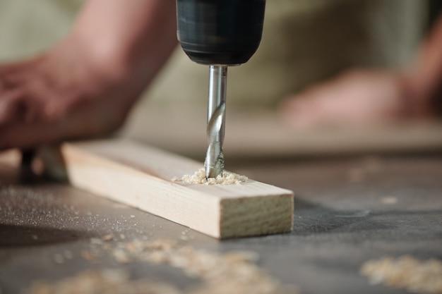 Close-up van onherkenbare timmerman die houten plank boort om gaten op de werkplek te maken
