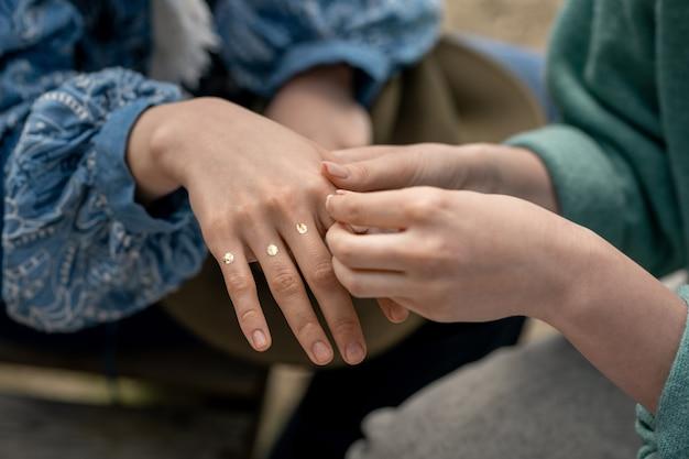 Close-up van onherkenbare vrouw die confetti-pailletten op vingers van meisje bevestigt terwijl zij zich voorbereiden op festival
