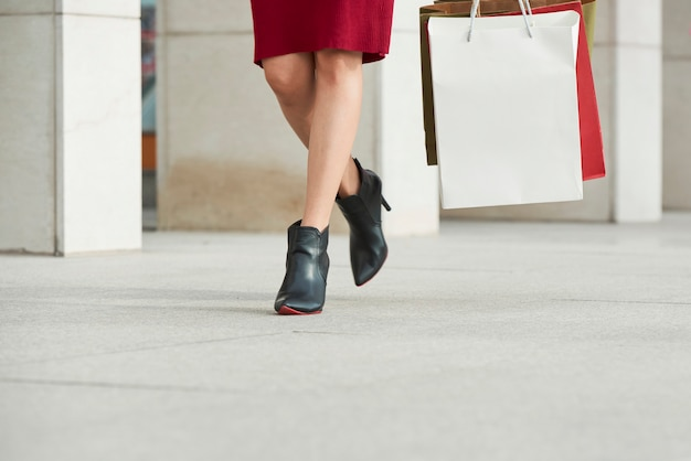 Close-up van onherkenbare vrouw op zwarte hakken die met kleurrijke boodschappentassen over straat loopt