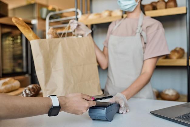 Close-up van onherkenbare vrouwelijke bediende van bakkerij in handschoenen die terminal geeft voor nfc-betaling in de winkel