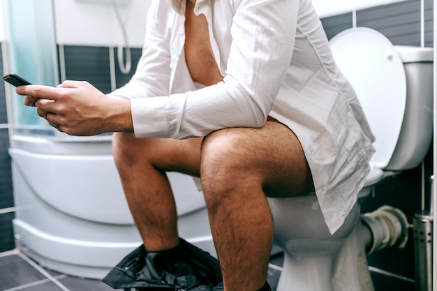 Close-up van onherkenbare zakenman die slimme telefoon gebruikt voor het schrijven of lezen van bericht terwijl hij op het toilet zit.