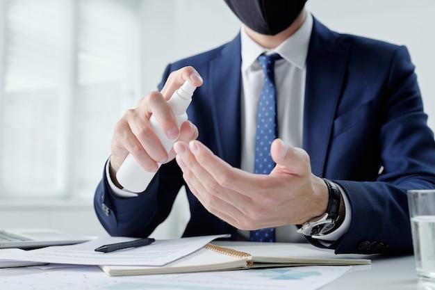 Close-up van onherkenbare zakenman zittend aan een bureau met blocnote en papieren en handen schoonmaken met ontsmettingsmiddel, coronaviruspreventie