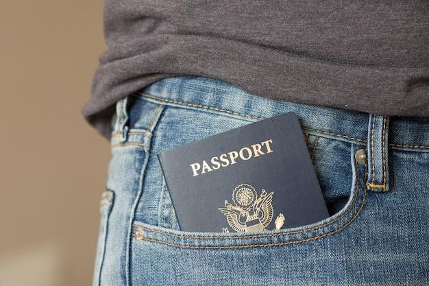 Close-up van ons paspoort in de jeanszak van de man klaar voor reizen en vakanties