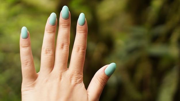 Close up van ontdekkingsreiziger vrouwelijke hand in groen regenachtig bos. survival reizen, lifestyle concept.