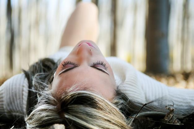 Close-up van ontspannen vrouw liggend op bladeren