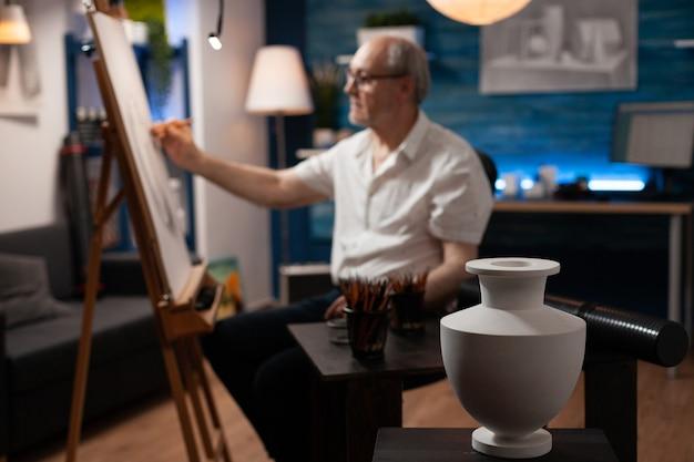 Close up van ontwerp van witte vaas op tafel met kunstinstrumenten