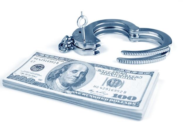 Close-up van open metalen handboeien, sleutels en stapel amerikaanse dollars contant geld geïsoleerd op witte achtergrond