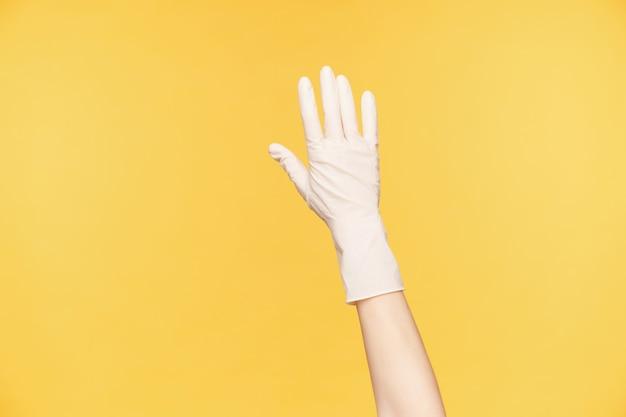 Close-up van opgeheven hand in witte rubberen handschoen poseren over oranje achtergrond, alle vingers afzonderlijk te houden. voorbereiding op de voorjaarsschoonmaak van huis
