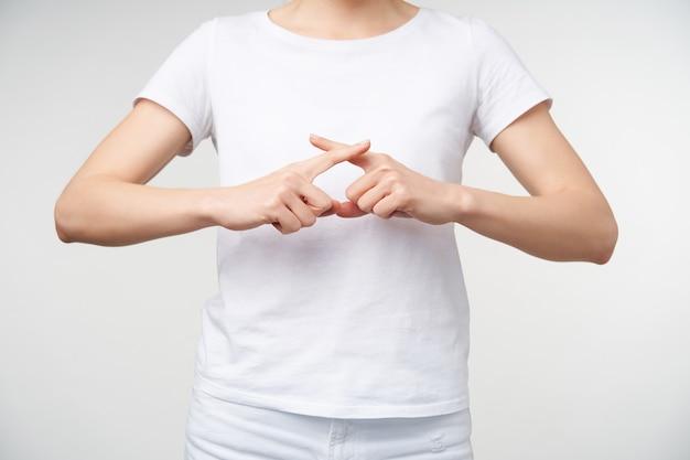 Close-up van opgeheven jonge vrouwenhanden die worden opgeheven terwijl ze gebarentaal spreken, wijsvingers kruisen terwijl woord ingenieur wordt weergegeven, geïsoleerd op witte achtergrond