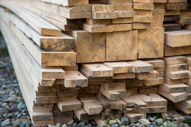 Close-up van opgestapelde stapel natuurlijke bruine ongelijke ruwe houten planken verlicht door felle zon. industrieel hout voor timmerwerk, bouw, reparatie en meubels, timmerhout voor de bouw.