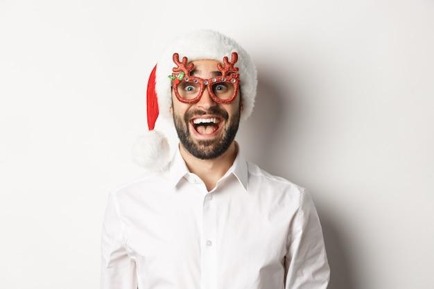 Close-up van opgewonden bebaarde man in kerstbril en kerstmuts kijken verbaasd over promo-aanbieding, wintervakantie advertentie concept, witte achtergrond.