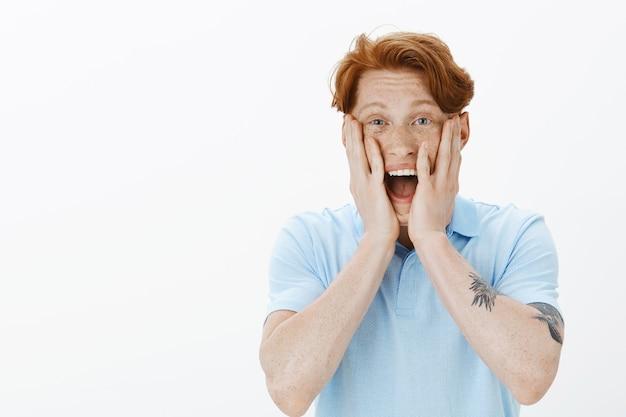 Close-up van opgewonden en verheugende roodharige man die lacht, ontvangt fantastisch nieuws