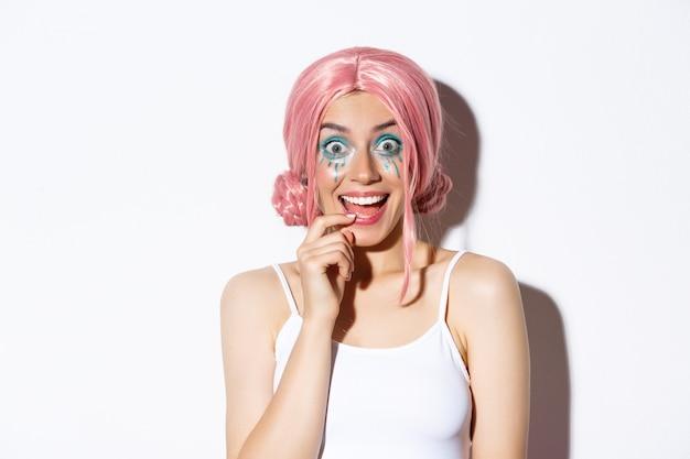 Close-up van opgewonden feestmeisje in roze pruik en lichte make-up op zoek onder de indruk, glimlachend en staren verrast, staande.
