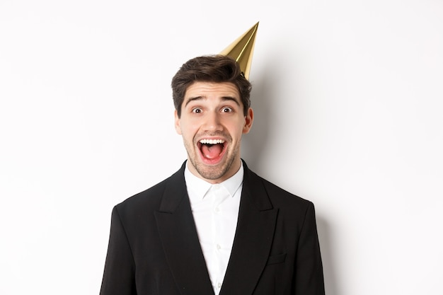 Close-up van opgewonden knappe jongen in trendy pak en feestmuts, verbaasd kijkend, wintervakantie vierend, staande tegen een witte achtergrond