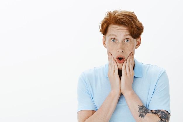 Close-up van opgewonden roodharige man die verbaasd kijkt, reageert op roddels