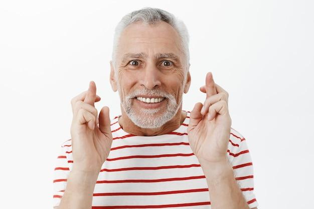Close-up van optimistische hoopvolle senior man, kruis vinger veel geluk, wens maken