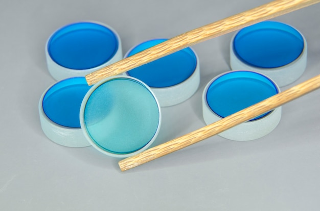 Close-up van optische spiegelsbatch met nadruk op geselecteerde door houten pincet