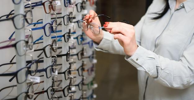 Close-up van optometrist, opticien die glazen geeft om te proberen