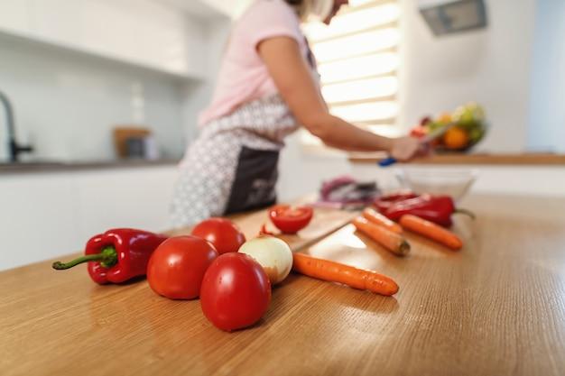 Close-up van organische verse tomaten, peper en wortelen op keukentafel.